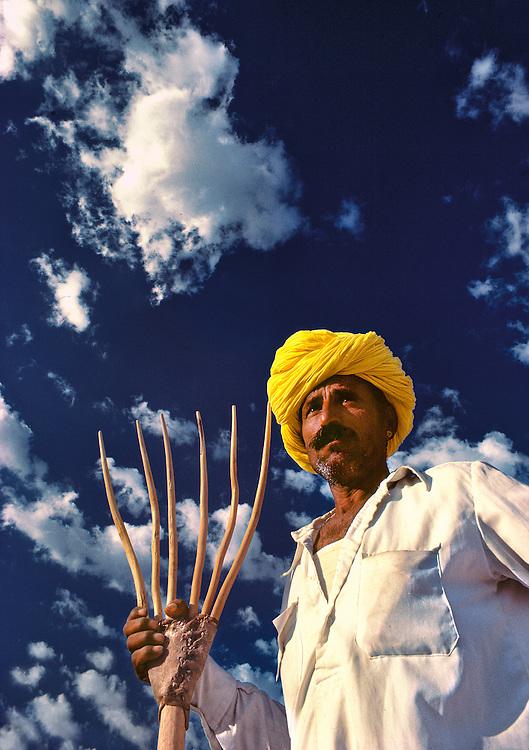 A farmer's brilliant yellow turban contrasts against a deep blue sky in the Great Thar Desert, near Jaiselmeer, India.