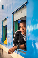 YANGON, MYANMAR - CIRCA DECEMBER 2013: Young burmese man looking away from a train window while it waits for departure in Yangon Central Railway Station
