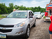 """26 JUNE 2020 - DES MOINES, IOWA: A girl leans out her window and waves to workers at Fair Food Friday in Des Moines. The 2020 Iowa State Fair, like many state fairs in the Midwest, has been cancelled this year because of the COVID-19 (Coronavirus) pandemic. The cancellation of the fair left many small vendors stranded with no income. Some of the fair food vendors in Iowa started """"Fair Food Fridays"""" on a property a few miles south of the State Fairgrounds. People drive up and don't leave their cars while vendors bring them the usual midway fare; corndogs, fried tenderloin sandwiches, turkey legs, deep fried Oreos, lemonaide and smoothies. Fair Food Friday has been very successful. The vendors serve 450-500 people per Friday and during the lunch rush people wait in line in their cars 30 - 45 minutes to place an order.    PHOTO BY JACK KURTZ"""
