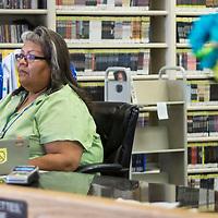 Henrietta Etsitty, a library clerk at the Octavia Fellin Public Library, checks the system for overdue books on Jul. 30, 2018.