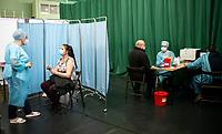 Siemiatycze, 19.04.2021. Punkt Szczepien Powszechnych w Siemiatyczach w hali sportowo-widowiskowej. Jest to jeden z 16 pilotazowych takich punktow w Polsce. Docelowo moze szczepic przeciwko COVID-19 500 osob dziennie. N/z podawanie szczepionki, z prawej kwalifikacja medyczna do szczepienia fot Michal Kosc / AGENCJA WSCHOD