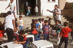 Teachers supervising nursery school children playing in playground,