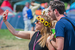 Early arrivals can enjoy the  blistering heat in sunglasses and fancy dress. The 2015 Glastonbury Festival, Worthy Farm, Glastonbury.