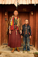 A senior monk and small boy pose in front of their home in Litang, China (Tibet).