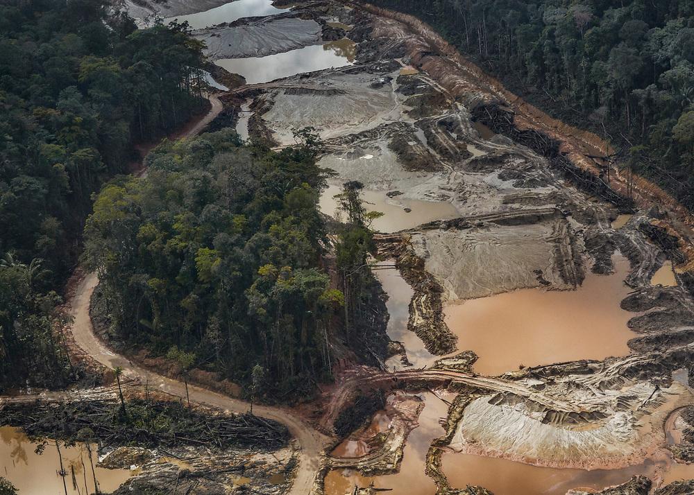 Saint-Elie, Guyane, 2015.<br /> <br /> Concession minière. Saint-Elie est un des plus anciens villages de l'intérieur guyanais, créé par l'orpaillage au XIXe siècle. Pratiquement déserté et très fortement enclavé, Saint-Élie a connu sa période de gloire avec la saga de l'orpaillage illégale au début des années 2000. Plusieurs centaines de clandestins Brésiliens s'y installent. Le bourg devient hors de contrôle. En 2008, l'opération Harpie menée par les Forces Armées en Guyane oblige les clandestins à quitter les lieux et 22 commerçants de Saint-Élie sont appelés à comparaître pour complicité d'orpaillage illégal. Saint-Élie devient un village fantôme avec ses 38 électeurs inscrits. Si le territoire de la commune s'étend sur 5680 km2, le bourg de Saint-Elie bâti à flanc de colline et assoupi sur un gisement d'or n'est plus propriétaire de l'intégralité de son foncier. Le village est maintenant cerné par des opérateurs miniers légaux.