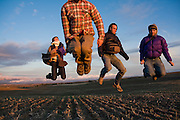 Four friends jump into the air in a field at sunset in the Palouse Valley near Spokane, Washington.