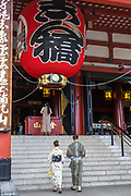 A Japanese couple dressed in kimono, enter the main hall of the Sensoji Buddhist temple in Asakusa, Tokyo, Japan. The temple was built during the Kamakura period in 645 CE and is the oldest and most important temple in Tokyo.