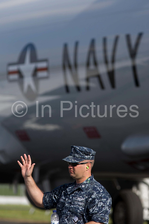 US Navy crewman guards a Poseidon jet aircraft, exhibited at the Farnborough Air Show, England. The two men in uniform stand below the large US Navy lettering on the patrol and surveillance jet's fuselage. The Boeing P-8 Poseidon (formerly the Multimission Maritime Aircraft or MMA) is a military aircraft developed for the United States Navy (USN). It conducts anti-submarine warfare (ASW), anti-surface warfare (ASUW), and shipping interdiction, along with an electronic signals intelligence (ELINT) role. This involves carrying torpedoes, depth charges, SLAM-ER missiles, Harpoon anti-ship missiles, and other weapons.