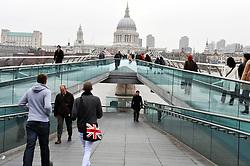 Commuters on Millennium Bridge, looking towards St Paul's. London UK