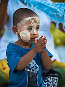 31 OCTOBER 2015 - YANGON, MYANMAR: A boy decorated with thanaka powder prays with his mother at Shwedagon Pagoda. Shwedagon Pagoda is officially known as Shwedagon Zedi Daw and is also called the Great Dagon Pagoda or the Golden Pagoda. It is a 99 metres (325 ft) tall pagoda and stupa located in Yangon, Burma. The pagoda lies to the west of on Singuttara Hill, and dominates the skyline of the city. It is the most sacred Buddhist pagoda in Myanmar and contains relics of four past Buddhas: the staff of Kakusandha, the water filter of Koṇāgamana, a piece of the robe of Kassapa and eight strands of hair from Gautama, the historical Buddha. The pagoda was built between the 6th and 10th centuries by the Mon people, who used to dominate the area around what is now Yangon (Rangoon). The pagoda has been renovated numerous times through the centuries. Millions of Burmese and tens of thousands of tourists visit the pagoda every year, which is the most visited site in Yangon.      PHOTO BY JACK KURTZ