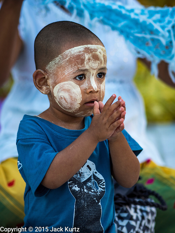 31 OCTOBER 2015 - YANGON, MYANMAR: A boy decorated with thanaka powder prays with his mother at Shwedagon Pagoda. Shwedagon Pagoda is officially known as Shwedagon Zedi Daw and is also called the Great Dagon Pagoda or the Golden Pagoda. It is a 99 metres (325ft) tall pagoda and stupa located in Yangon, Burma. The pagoda lies to the west of on Singuttara Hill, and dominates the skyline of the city. It is the most sacred Buddhist pagoda in Myanmar and contains relics of four past Buddhas: the staff of Kakusandha, the water filter of Koṇāgamana, a piece of the robe of Kassapa and eight strands of hair from Gautama, the historical Buddha. The pagoda was built between the 6th and 10th centuries by the Mon people, who used to dominate the area around what is now Yangon (Rangoon). The pagoda has been renovated numerous times through the centuries. Millions of Burmese and tens of thousands of tourists visit the pagoda every year, which is the most visited site in Yangon.      PHOTO BY JACK KURTZ