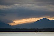 A lone sailboat in Puget Sound at sunset in Seattle, Washington.