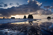 Sea stacks at sunset with wavy patterns of wet sand in the foreground and dramatic clouds above, Second Beach, Olympic National Park, Washington.