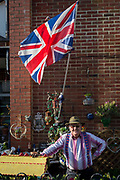 A portrait of a local patriotic man in his garden wearing Union Jack braces and standing beneath the national flag, on 29th April 2017, at Hastings, East Sussex, England.