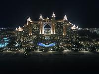 Aerial view of the luxurious Palm Jumeirah Atlantis Hotel at night in Dubai, United Arab Emirates.