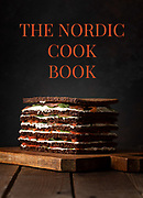 Cook book cover showing a salmon pie composed of several alternating layers of rye bread, cream cheese flavored with dill, slices of smoked salmon and tender spinach leaves.