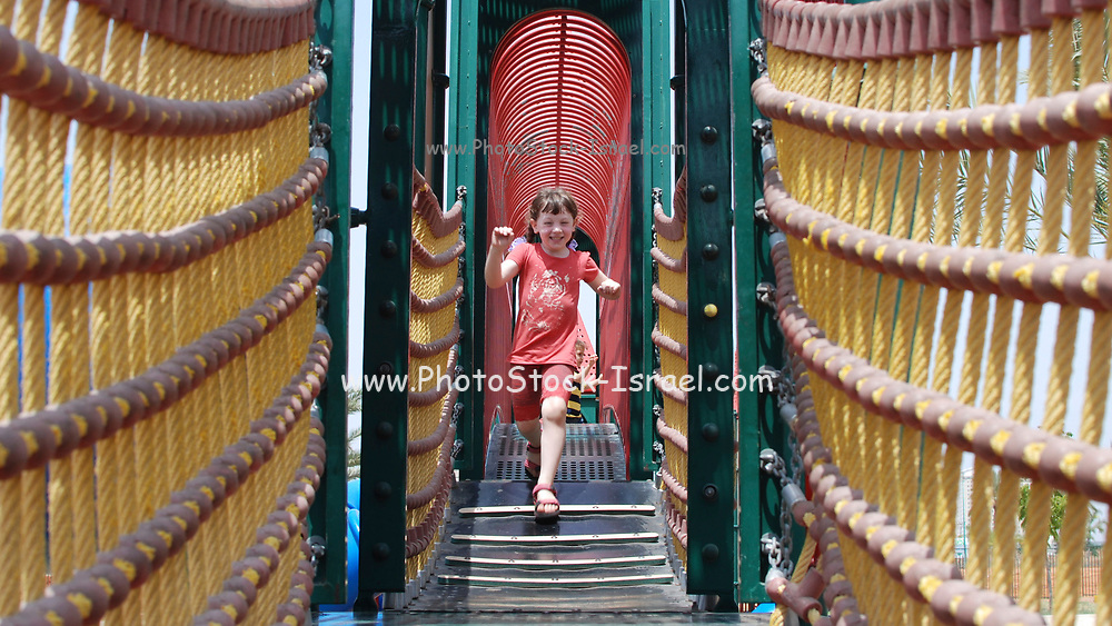An excited young Girl of 5 runs on a rope bridge in a play ground Model release available