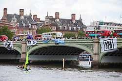 © Licensed to London News Pictures. 15/06/2016. London, UK. Supporters of the Remain Campaign drop banners from Westminster Bridge as a flotilla of fishing trawlers led by UKIP leader Nigel Farage arrives at Westminster. The flotilla is organised by the 'Fishing for Leave' campaign, founded by Scottish fisherman, which argues that the UK's fishing industry would be better off outside the EU, but with the same status as Iceland or Norway when fishing quotas are negotiated. Photo credit: Rob Pinney/LNP