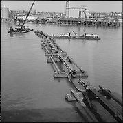 """9904-B02-5.  Dredge pipe & pontoons holding up electric cable at Crown Mills, March 26, 1957"""" caption published in the Oregonian March 26, 1957 pg. 15 """"Tug Plucks Power Cables to aid River Dredging."""" (Cable went from Crown Mills to the Permanente Cement plant. 120mm negatives. View looking west, showing the east bank of the Willamette River.)"""