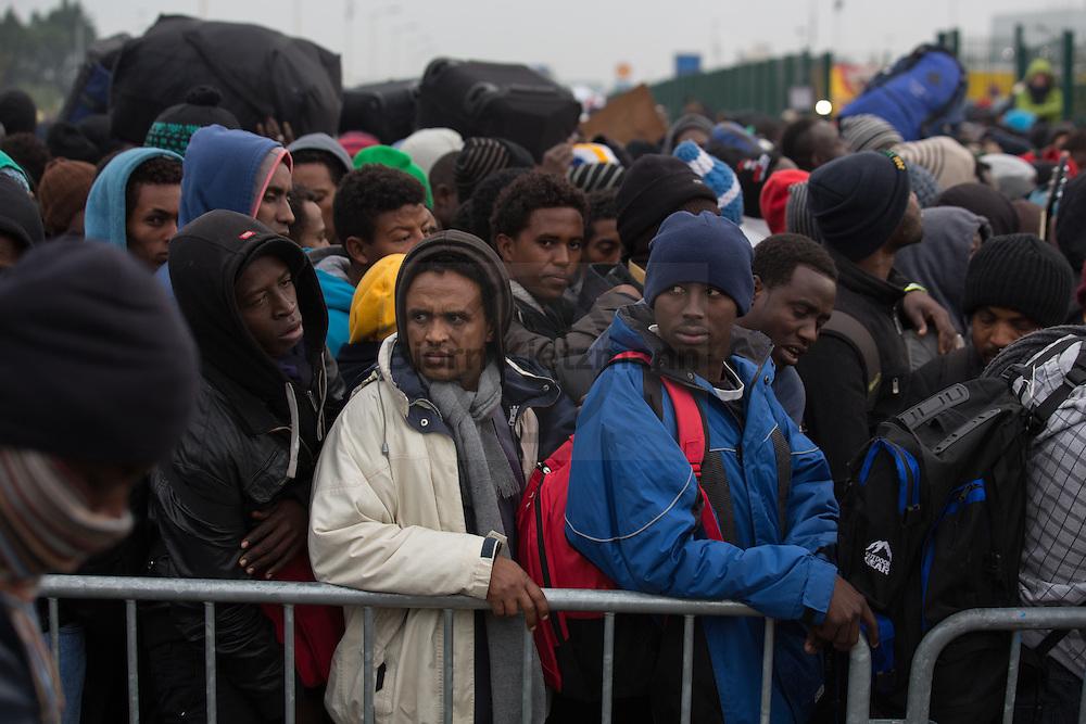 """Calais, Pas-de-Calais, France - 24.10.2016    <br />  <br /> Refugees line up at the registration center to get in busses. Start of the eviction on the so called """"Jungle"""" refugee camp on the outskirts of the French city of Calais. Refugees and migrants leaving the camp to get with buses to asylum facilities in the entire country. Many thousands of migrants and refugees are waiting in some cases for years in the port city in the hope of being able to cross the English Channel to Britain. French authorities announced a week ago that they will evict the camp where currently up to up to 10,000 people live.<br /> <br /> <br /> Fluechtlinge stehen vor dem Registrierungscenter um in Busse steigen zu koennen. Beginn der Raeumung des so genannte """"Jungle""""-Fluechtlingscamp in der französischen Hafenstadt Calais. Fluechtlinge und Migranten verlassen das Camp um mit Bussen zu unterschiedlichen Asyleinrichtungen gebracht zu werden. Viele tausend Migranten und Fluechtlinge harren teilweise seit Jahren in der Hafenstadt aus in der Hoffnung den Aermelkanal nach Großbritannien ueberqueren zu koennen. Die franzoesischen Behoerden kuendigten vor einigen Wochen an, dass sie das Camp, indem derzeit bis zu bis zu 10.000 Menschen leben raeumen werden. <br /> <br /> Photo: Bjoern Kietzmann"""