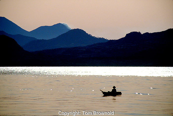 Local Guatemalan in his boat on Lake Atitlan with Volcán Atitán smoldering in the background.
