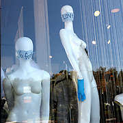 Mannequins wearing safety masks and gloves are displayed in a boutique store window that is closed due to the non-essential business order placed by the Orange County Government on Saturday, March 28, 2020 in Winter Park, Florida. (Alex Menendez via AP)