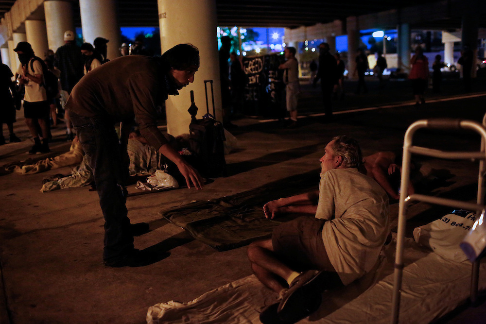 Protester William Estrella, left, talks with a homeless man after he and other protesters handed out sandwiches under an underpass in Tampa, Fla. during the 2012 Republican National Convention on August 29, 2012. The demonstrators took sandwiches to the homeless, picked up trash off of the street and spoke out against police brutality.