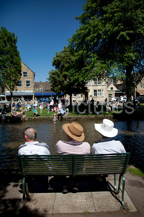Sitting by the stream at Bourton-on-the-Water in The Cotswolds, Gloucestershire, UK.  It is known as the 'Venice of the Cotswolds' because of the bridge-spanned stream that runs through the village, this is one of the most popular places to visit in the area. Popular with both the English themselves and international visitors from all over the world, the area is well known for gentle hillsides 'wolds', outstanding countryside, sleepy ancient limestone villages, historic market towns and for being so 'typically English' where time has stood still for over 300 years. Throughout the Cotswolds stone features in buildings and stone walls act as a common thread in seamlessly blending the historic towns & villages with their surrounding landscape. One of the most 'quintessentially English' and unspoiled regions of England.