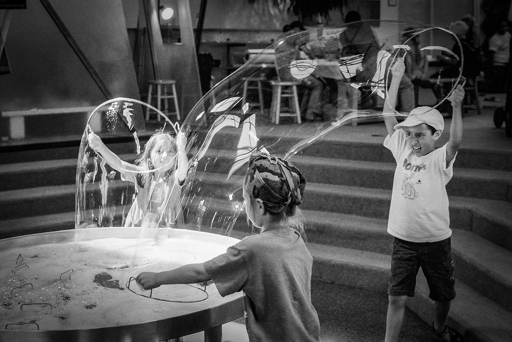 Kids create big bubbles with wands.