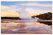 Looking at steam rising from the Excelsior Geyser Crater as seen from the Grand Prismatic Spring at sunset; Yellowstone National Park, Midway Geyser Basin, Wyoming, USA