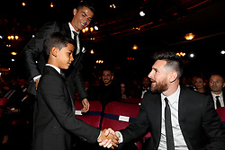 Lionel Messi (right) shakes hands with Cristiano Ronaldo Jr (left) as Cristiano Ronaldo (top) looks on