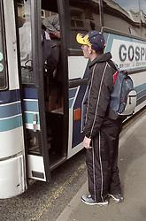 Homeless teenage boy waiting to climb aboard coach,