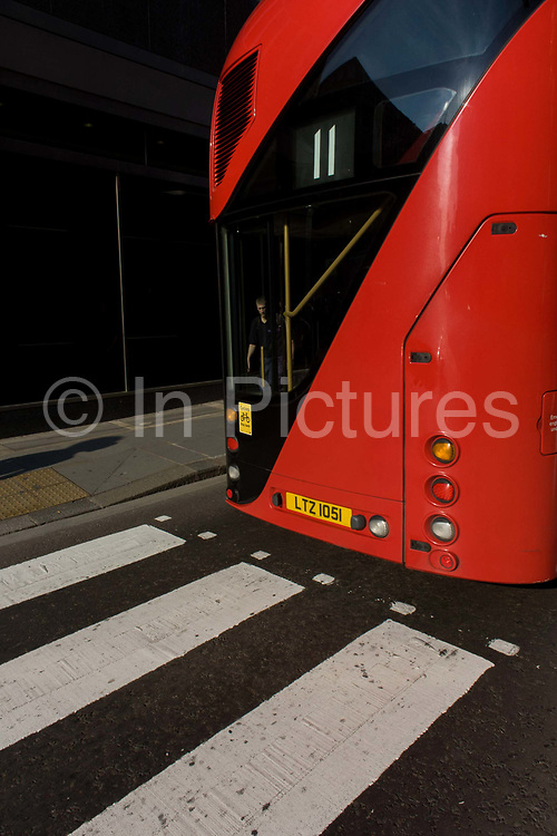 Repetition and visual pun of stripes from zebra crossing and number 11 Routemaster bus. As a visual pun of stripes and straight parallel lines, the eleven and white bars of the zebra crossing can be seen as a coincidence, a street trick. The hybrid NB4L, or the Borismaster, New Routemaster or Boris Bus, is a 21st century replacement of the iconic Routemaster as a bus built specifically for use in London and is said to be 40 per cent more fuel efficient than conventional diesel buses. The brainchild of London's Conservative mayor Boris Johnson, its funding has been controversial amid massive fare increases in transport.