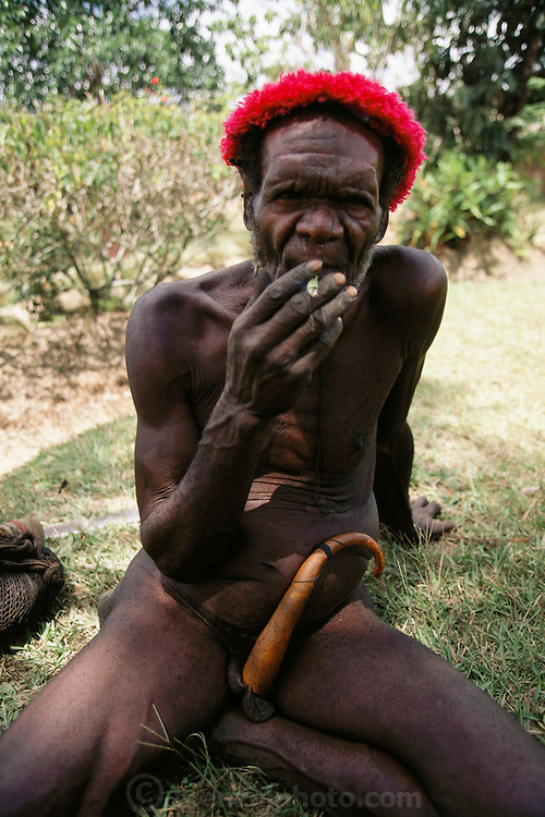 Local Dani tribesman wears a penis gourd, called a horum, and a fuzzy red hat,  smokes a hand rolled tobacco cigarette, in Soroba Village in the central highlands of the South Baliem Valley, Irian Jaya, Indonesia. Since the making of this photograph, Irian Jaya was renamed Papua.