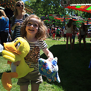 A young girl shows delight with her cuddly toys won during the May Fair at Saint Mark's Church, New Canaan, Connecticut, USA. 12th May 2012. Photo Tim Clayton