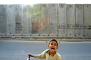 A young Palestinian boy in front of the Wall. Political statements are common decoration along the wall being built by the Israelis to separate Palestine and Israel.