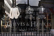 Made-to-measure suits are on display in the window of quality taylor Gieves & Hawkes on Savile Row during the third lockdown of the Coronavirus pandemic, on 5th February 2021, in London, England.