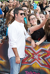 Image ©Licensed to i-Images Picture Agency. 01/08/2014. London, . RED CARPET ARRIVALS AT THE X FACTOR 2014. Simon Cowell gets a selfie with a fan as he arrives at the X-Factor auditions at Wembley Arena. Picture by Daniel Leal-Olivas / i-Images