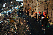 Un grupo de mineros que han terminando su jornada de trabajo caminan por uno de los principales accesos a la ciudad de Rinconada.