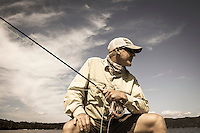 male fly angler site fishing against a bright blue sky, lake champlain