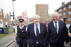 © Licensed to London News Pictures. 03/04/2014. London, UK. In picture: Boris Johnson (L) and Richard Cornelius. Residents of Barnet protest outside the Community Center against the Mayor of london Boris Johnson who is attenting for the inauguration of new council houses. Photo credit : Andrea Baldo/LNP