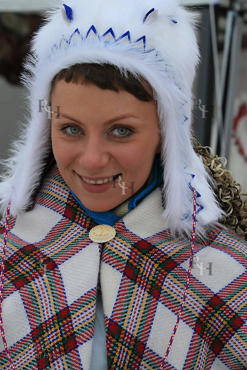 Young Russian Sami woman models fur hat made from arctic fox at outdoor market in Kautokeino, Finnmark, Norway.