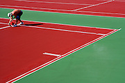 Jonathon Bushek of Atlas Track & Tennis in Tualatin, Ore. paints the lines in on one of eight tennis courts at Kamiakin High School in Kennewick, Wash. The lines were the last step of maintenance on the courts.