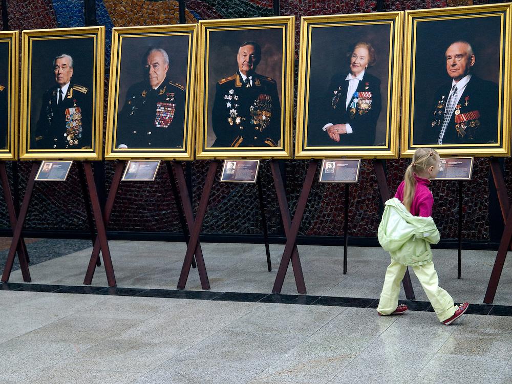 """Mädchen vor einer Ausstellung mit Portraits von Veteranen aus dem 2. Weltkrieg im Museum des Großen Vaterländischen Krieges in Moskau. Das Museum befindet sich auf dem Berg """"Poklonnaja Gora"""". <br /> <br /> Girl infront of an exhibition with portraits of WW II veterans in the Museum of the Great Patriotic War in Moscow at Poklonnaya Gora (Bowing Hill)."""