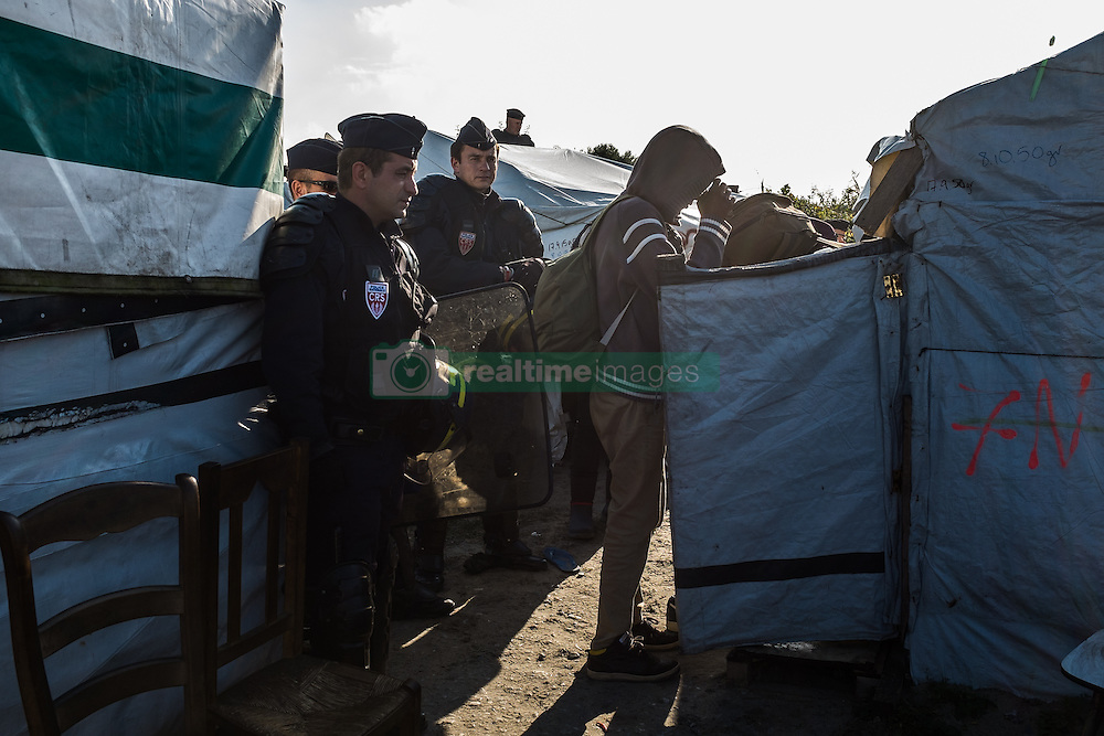 October 25, 2016 - Calais, France - A police officer supervises during the evection of the Calais Jungle a Migrant who packs his belongings  in Calais, France, on 25 October 2016. Up to the evening, about 4,000 migrants from the Refugee camp on the coast at the English Channel were distributed to several regions in France. The police have begun to tear down the huts and tents in the camp. (Credit Image: © Markus Heine/NurPhoto via ZUMA Press)