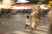 young mother running with child at the zebra crossing in Shibuya