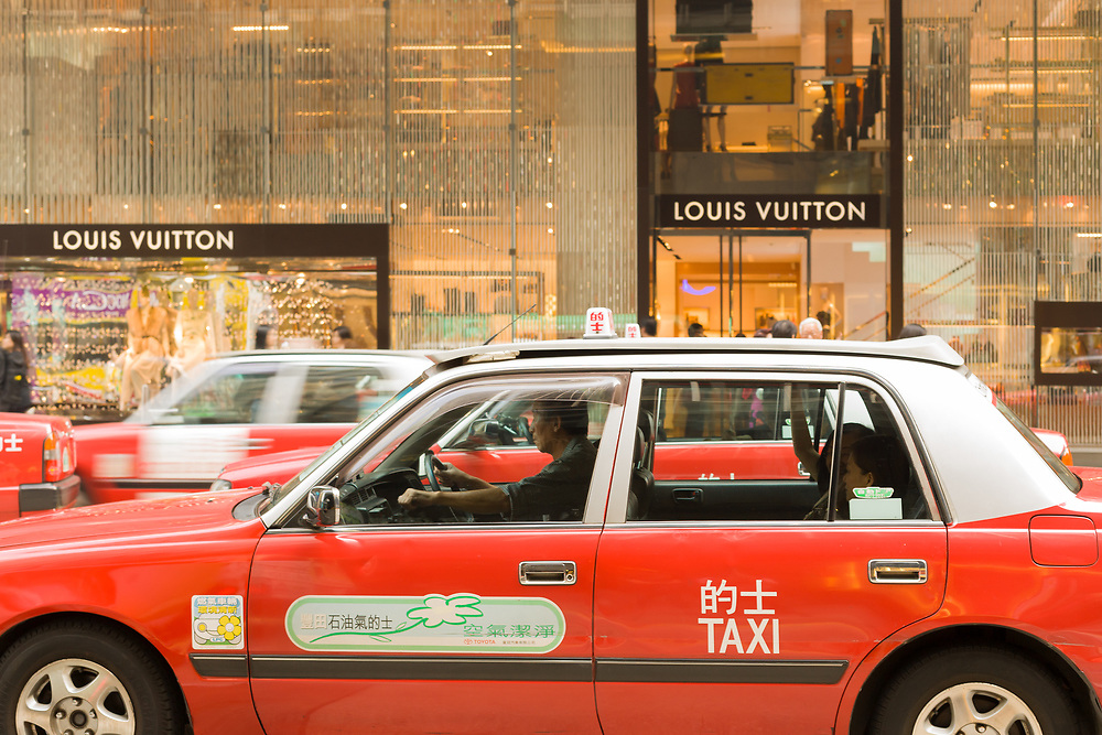 Hong Kong, Central district, China, Asia - Traditional red taxis in front of a Louis Vuitton store at Central district Hong Kong.
