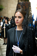 """A woman walks in formal black attire and a lace """"mantilla"""" in a procession during the Holy Week in Granada, Andalusia. Spain"""