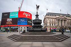 © Licensed to London News Pictures. 20/03/2020. London 09.59am, UK. A man looks at his phone in a deserted Piccadilly Circus on the first day of Spring which would normally be teaming with tourists and workers now resembles a ghost town as the Coronavirus crisis continues. Photo credit: Alex Lentati/LNP