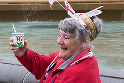 Trafalgar Square, London, June 12th 2016. Rain greets Londoners and visitors to the capital's Trafalgar Square as the Mayor hosts a Patron's Lunch in celebration of The Queen's 90th birthday. PICTURED: A woman raises a toast with her tea.